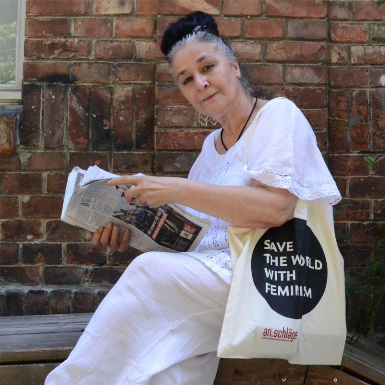 Eine Frau sitzt auf einer bank und hat eine an.schläge Tasche über der Schulter